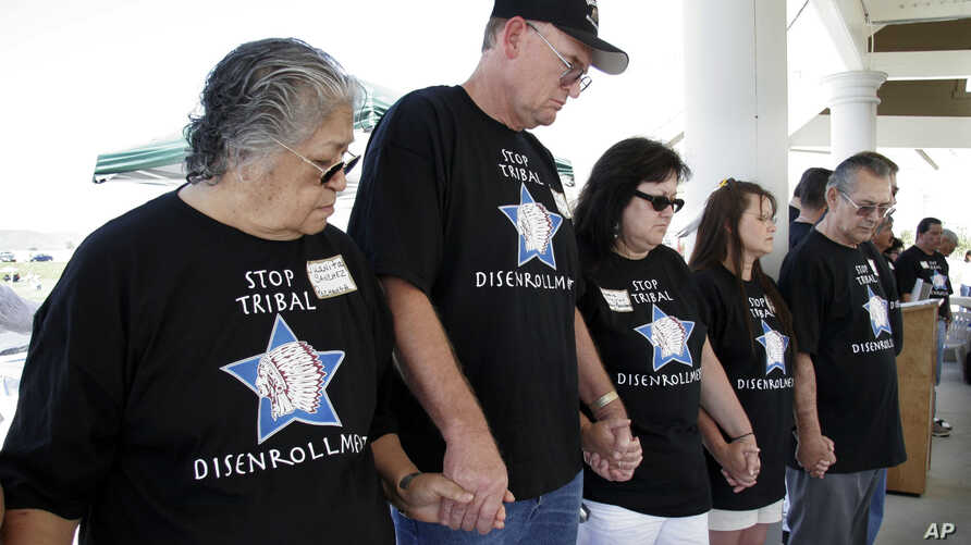 FILE - Protesters hold hands in prayer in Temecula, Calif., at a rally protesting the disenrollment of tribal members, Saturday, May 21, 2005. More than a hundred ousted members of tribes from California and five other states gathered to denounce bei