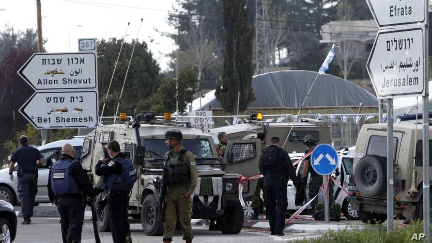 Israeli soldiers and police officers examine the scene of an attack in the Gush Etzion junction in the West Bank, March 18, 2016.
