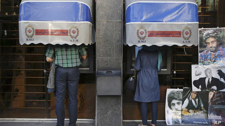 FILE - Iranians use ATM machines of Bank Melli Iran in downtown Tehran, Iran, April 4, 2015.