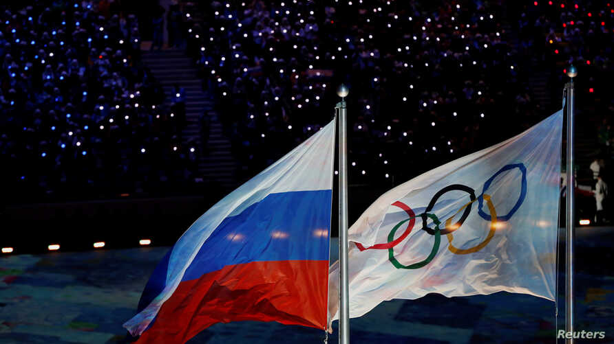 The Russian national flag flutters next to the Olympics flag during the closing ceremony for the 2014 Sochi Winter Olympics, Feb. 23, 2014.