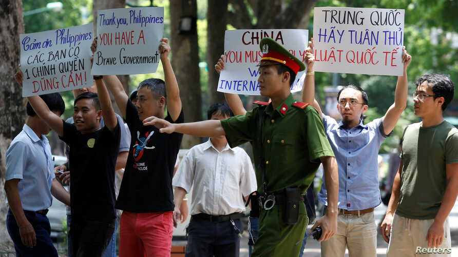 A policeman tries to stop anti-China protesters holding placards during a demonstration in front of the Philippines embassy in Hanoi, Vietnam July 17, 2016. REUTERS/Kham