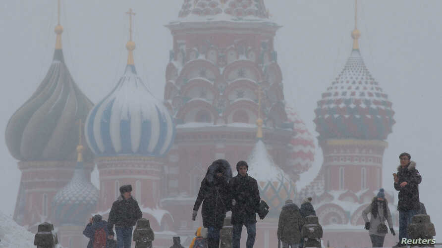 FILE - People walk in Red Square during heavy snowfall in Moscow, Russia, Jan 27, 2019.