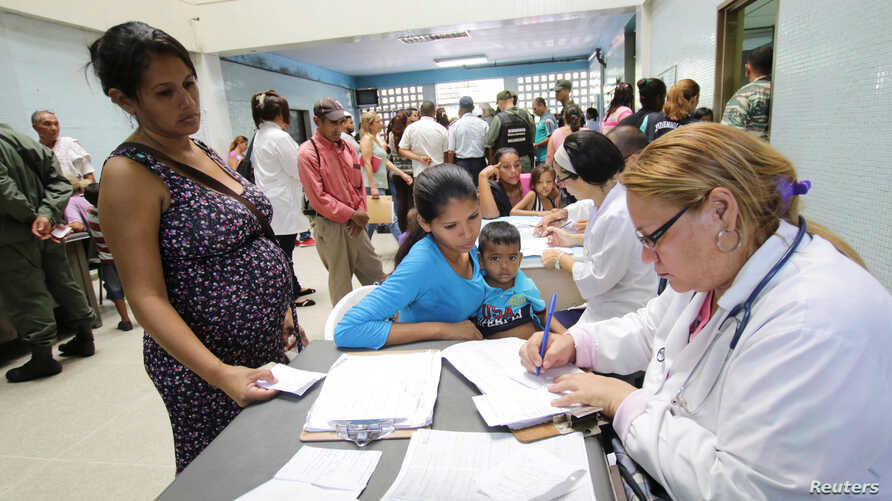 FILE - A doctor assists people looking for treatment for malaria at a health center in San Felix, Venezuela, Nov. 3, 2017.