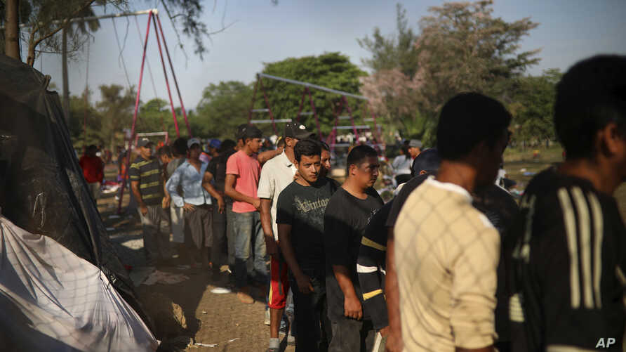 Men line up to receive a donated breakfast, at a sports center where Central American migrants traveling with a U.S. border-bound caravan have been camped out, in Matias Romero, Oaxaca State, Mexico, April 4, 2018.