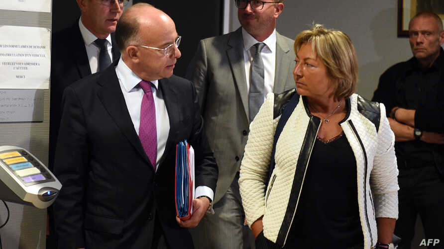 """French Interior Minister Bernard Cazeneuve (L) speaks to Calais Mayor Natacha Bouchart after a meeting on the dismantle of the """"Jungle"""" migrant camp on Sept. 2, 2016 in Calais, northern France."""