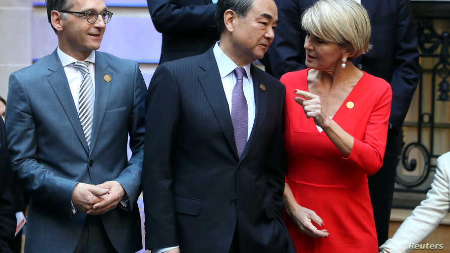 FILE - Australia's FM Julie Bishop talks to her counterpart of China, Wang Yi, as Germany's FM Heiko Maas watches, at the G20 Meeting of Foreign Affairs Ministers in Buenos Aires, Argentina, May 21, 2018.