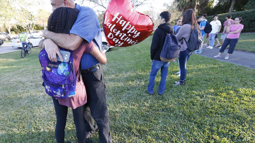 Family members embrace following a shooting at Marjory Stoneman Douglas High School, Feb. 14, 2018, in Parkland, Fla.