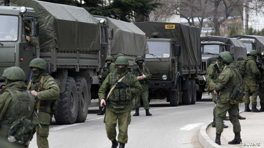 Armed servicemen wait near Russian army vehicles outside a Ukrainian border guard post in the Crimean town of Balaclava, March 1, 2014.
