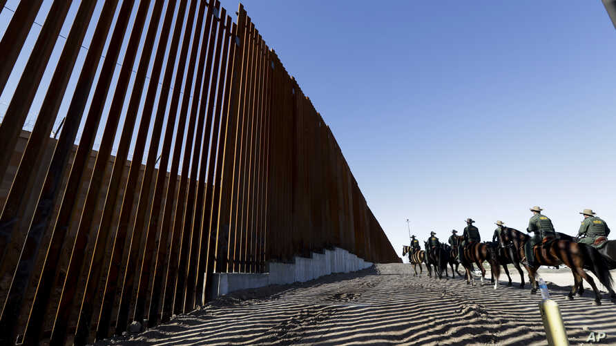 Mounted Border Patrol agents ride along a newly fortified border wall structure, Oct. 26, 2018, in Calexico, California.