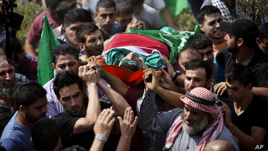 Palestinians carry the body of Huthaifa Suleiman, 18, during his funeral in the Bal'a village near the West Bank city of Tulkarem, Oct. 5, 2015.