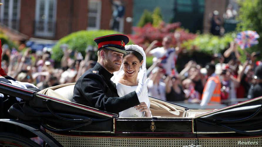 Prince Harry and his wife, Meghan Markle, wave as they ride a horse-drawn carriage after their wedding ceremony at St George's Chapel in Windsor, Britain, May 19, 2018.