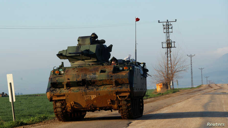 Turkish soldiers ride in an armoured personnel carrier (APC) as they patrol in a village near the Turkish-Syrian border in Hatay province, Turkey, Jan. 28, 2018.