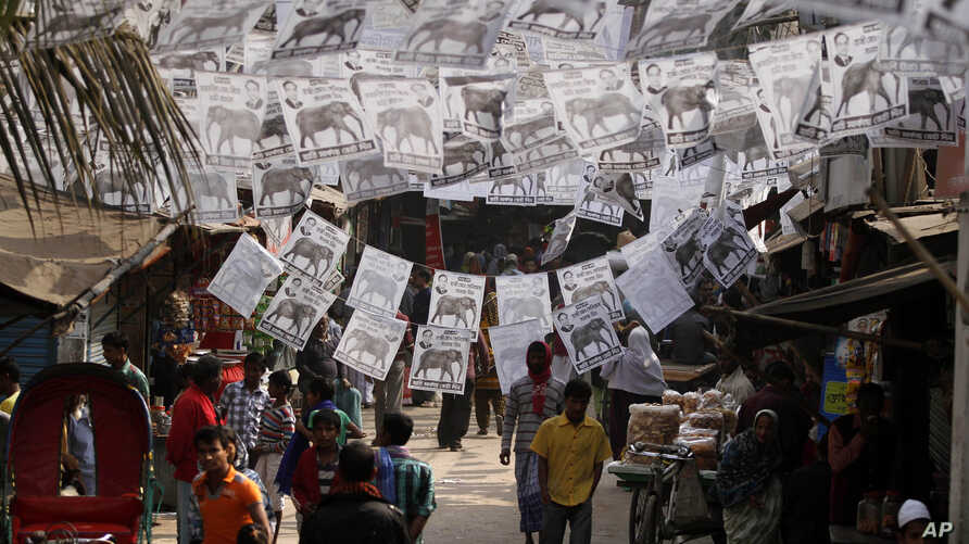People walk near posters with portraits of contesting candidates urging voters to cast their ballot for their respective parties hung overhead on a street in Dhaka, Bangladesh, Jan. 3, 2014.