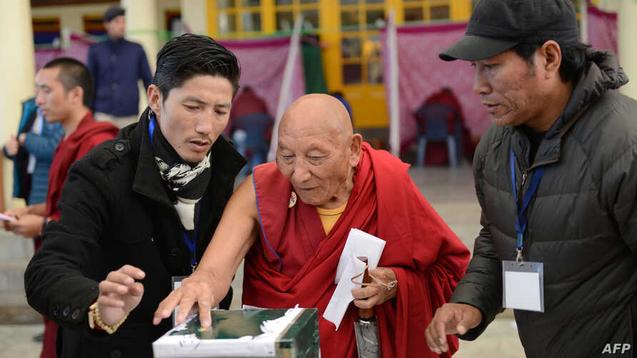 FILE - Palden Gyatso is guided as he casts his vote to elect a sikyong (prime minister) of the Central Tibetan Administration and lawmakers in McLeod Ganj, March 20, 2016. The Tibetan monk died Nov. 30, 2018, in Dharamsala, India, at age 85.