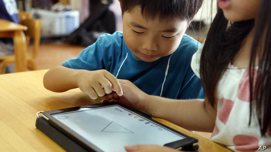 FILE - Children work on a digital program at Coby Preschool in Yoshikawa, suburban Tokyo, on an assignment, which was to draw on a triangle on an iPad, July 12, 2018.
