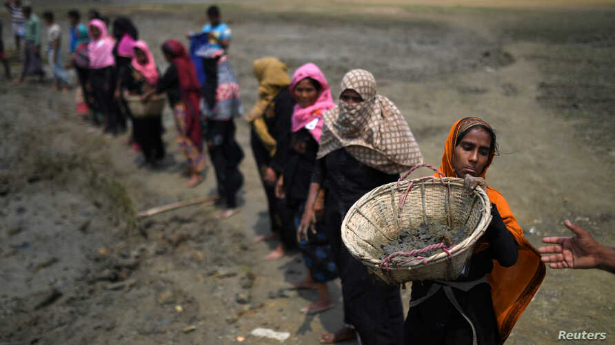 FILE - Rohingya refugee women carry baskets of dried out mud from the riverbed to help raise the ground level of their camp in preparation for monsoon season, in Shamlapur refugee camp, in Cox's Bazaar, Bangladesh, March 24, 2018.