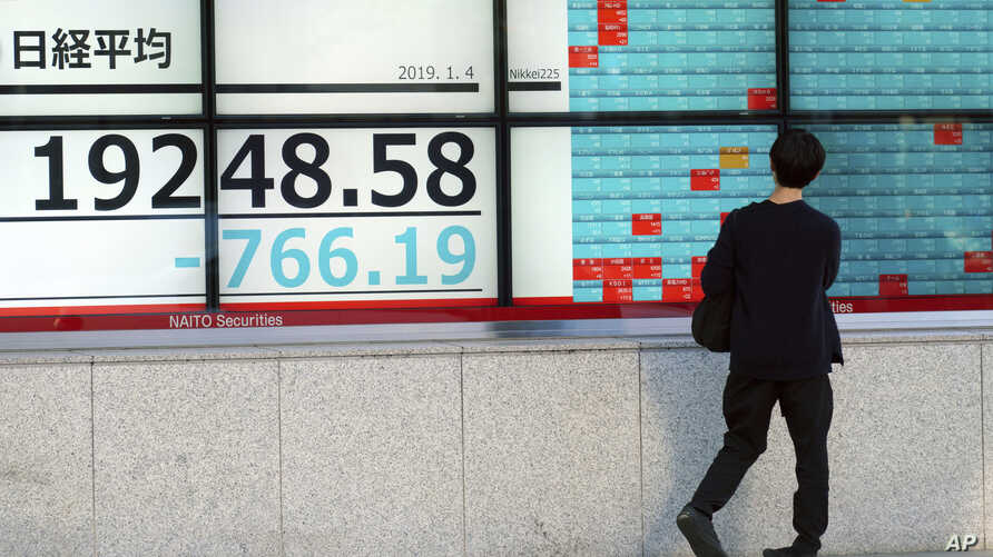 A man looks at an electronic stock board showing Japan's Nikkei 225 index at a securities firm in Tokyo Friday, Jan. 4, 2019. Japanese markets have tumbled as they reopened after the New Year holidays, while other Asian indexes are mixed after a tech