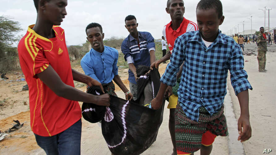 People carry away the body of a man killed in a suicide car bomb attack, near the defense ministry compound in Mogadishu, April 9, 2017.