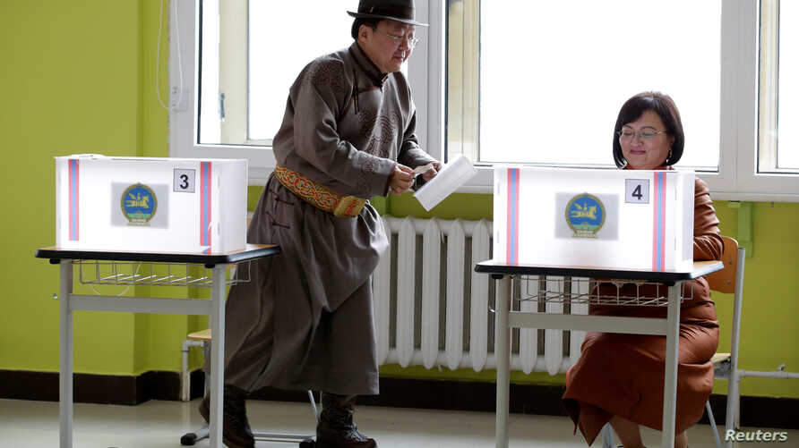 Mongolian President Tsakhiagiin Elbegdorj  (L) and his wife Bolormaa Khajidsuren attend voting for the parliamentary elections at a polling station in Ulaanbaatar, Mongolia, June 29, 2016.