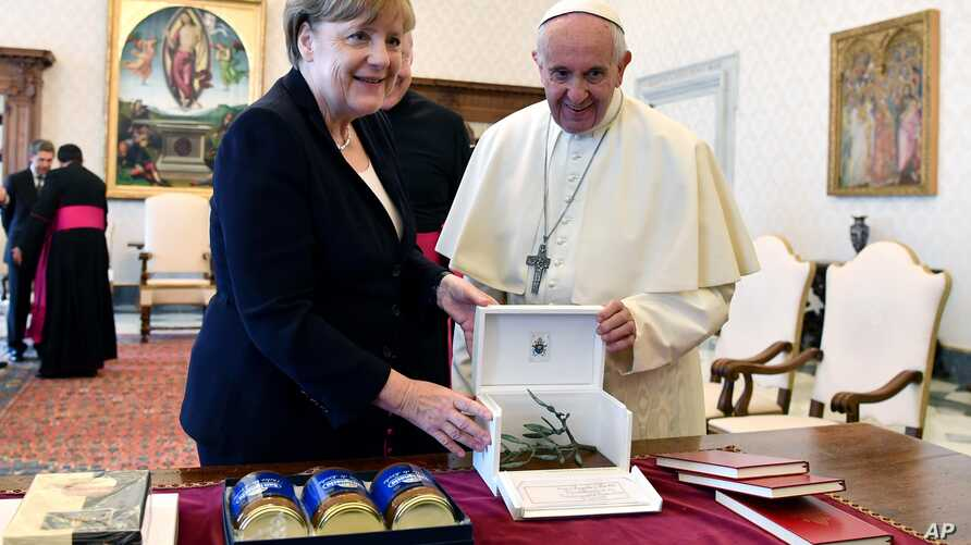Pope Francis and German Chancellor Angela Merkel exchange gifts on the occasion of their private audience, at the Vatican, June 17, 2017.