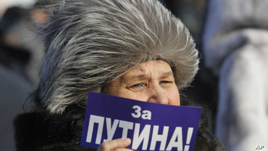 """A demonstrator holds a poster reading: """"For Putin!"""" during a rally in support of Putin's candidacy to the presidency in the March 4th election, in St.Petersburg, Russia, Saturday, Feb. 18, 2012."""
