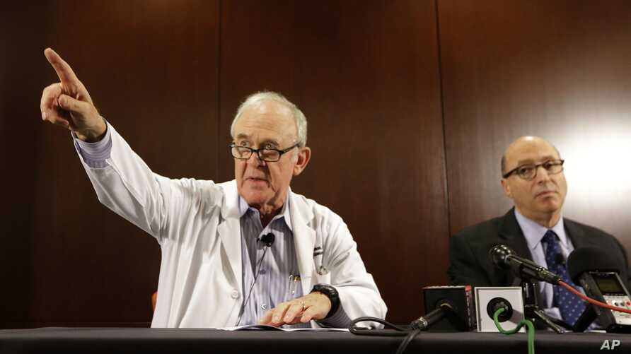 Dr. Edward Goodman, left, epidemiologist at Texas Health Presbyterian Hospital Dallas, points to a reporter for a question as Dr. Mark Lester looks on during a news conference about an Ebola infected patient they are caring for in Dallas, Sept. 30, 2...