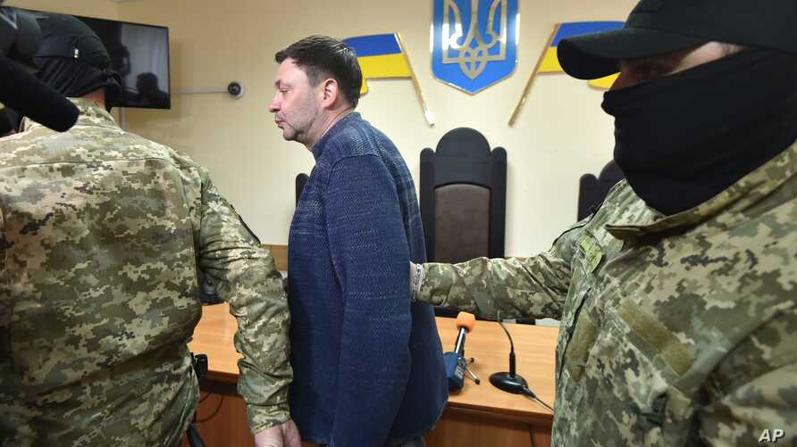 FILE - A masked police officer escorts a defendant out of a courtroom in the southern Ukrainian city of Kherson, May 17, 2018.