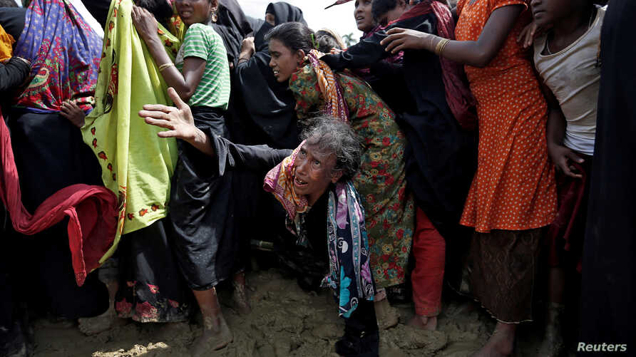 A Rohingya refugee reacts as people scuffle while waiting to receive aid in Cox's Bazar, Bangladesh, Sept. 26, 2017.