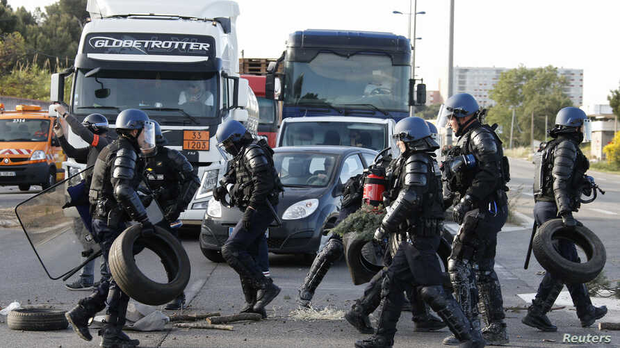 French gendarmes remove branches, wood pallettes and tyres after striking workers blocked roads near the oil refinery at Fos-sur-Mer, near Marseille, France, May 24, 2016 with France's hardline CGT and FO unions toughening their stance against labor