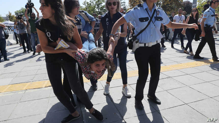 Riot police officers detain protesters during the trial of two Turkish educators, who went on a hunger strike over their dismissal under a government decree following last year's failed coup, outside a courthouse in Ankara, Turkey, Sept. 14, 2017.