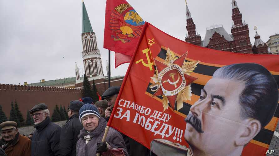 Communist party supporters carry flags with portraits of Soviet dictator Josef Stalin during a demonstration marking the 100th anniversary of the 1917 Bolshevik revolution in Red Square, in Moscow, Russia, Nov. 5, 2017.