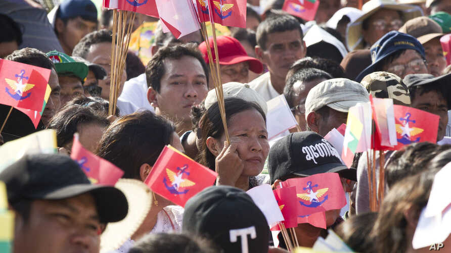 Participants holding national and military flags attend a march supporting the country's military and government servants, Oct. 29, 2017, in Yangon, Myanmar.
