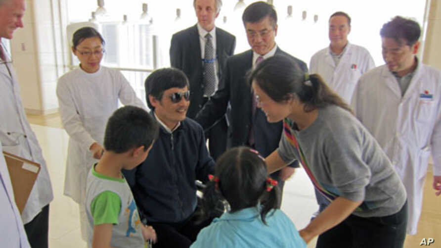 Blind activist Chen Guangcheng (C) speaks with his wife Yuan Weijing (2nd R) and children as U.S. ambassador to China Gary Locke (facing camera, 3rd R) and U.S. Assistant Secretary of State for East Asian and Pacific Affairs Kurt Campbell (facing cam