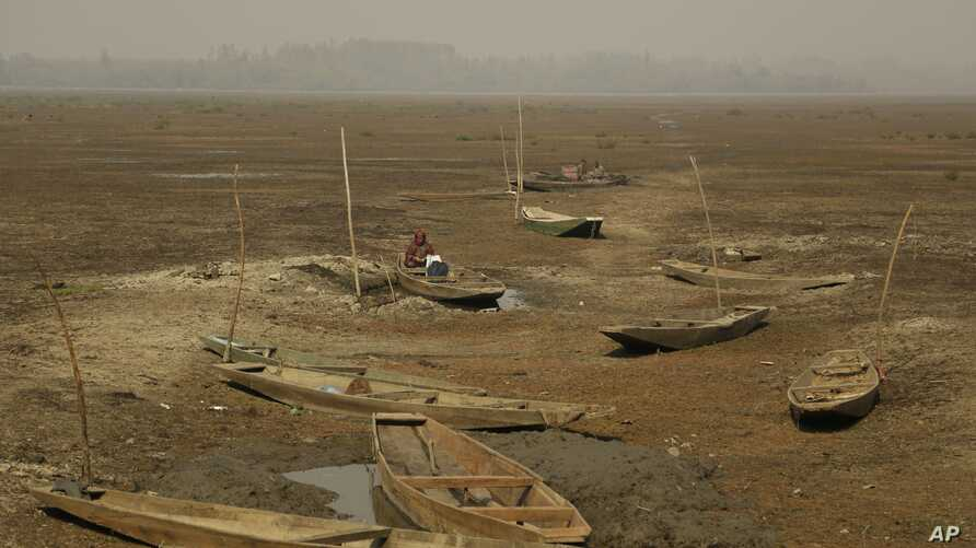 A Kashmiri woman works as she sits inside a boat at a dried portion of Wular Lake, northeast of Srinagar, Indian-controlled Kashmir, Oct. 29, 2016.