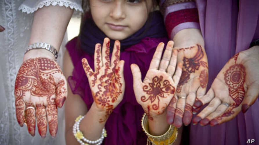Muslim women a girl show their hands decorated with Henna, after Eid al-Fitr prayers in Bucharest, Romania, Tuesday, Aug 30, 2011.