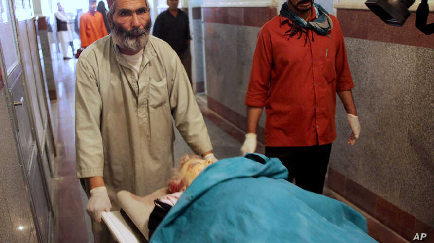 Afghan medical workers move the dead body of a foreign female aid worker who was employed by the International Assistance Mission, in Herat, west of Kabul, Afghanistan, July 24, 2014.
