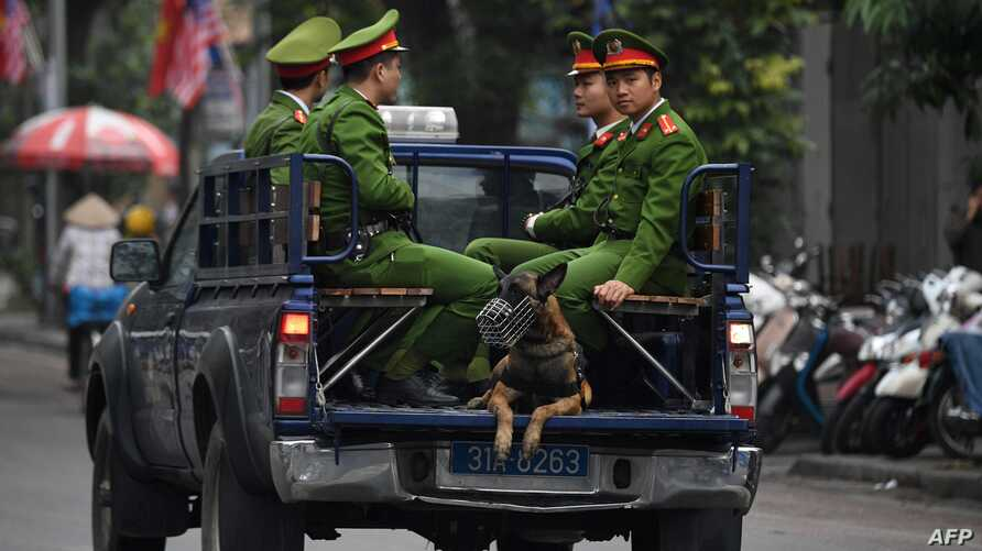 FILE - Policemen sit in the back of a truck in Hanoi, Vietnam, March 1, 2019.