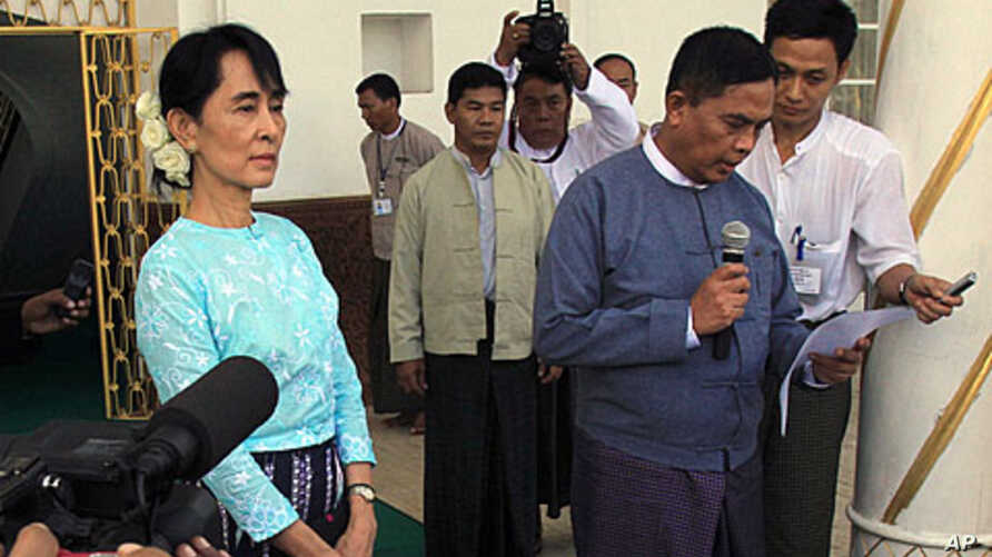 Burma's Labor Minister, Aung Kyi, right, reads out a statement after meeting with democracy leader Aung San Suu Kyi, left, during a press conference in Yangon, Burma,  October 30, 2011.