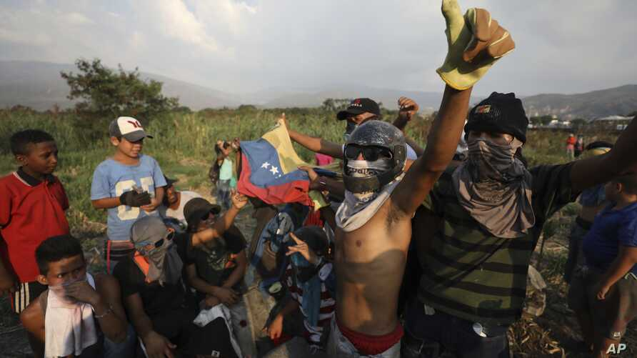 Venezuelan migrants near the Simon Bolivar International Bridge plead for people to support them with food and water so they can continue protesting in La Parada near Cucuta, Colombia, Sunday, Feb. 24, 2019, on the border with Venezuela.
