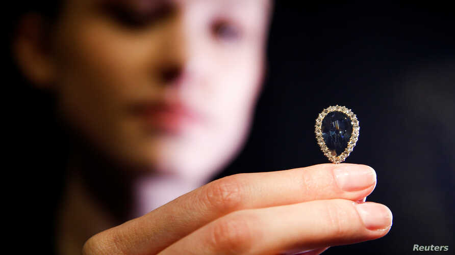 FILE - A model poses with The Farnese Blue diamond at Sotheby's auction house in London, Britain, April 6, 2018.