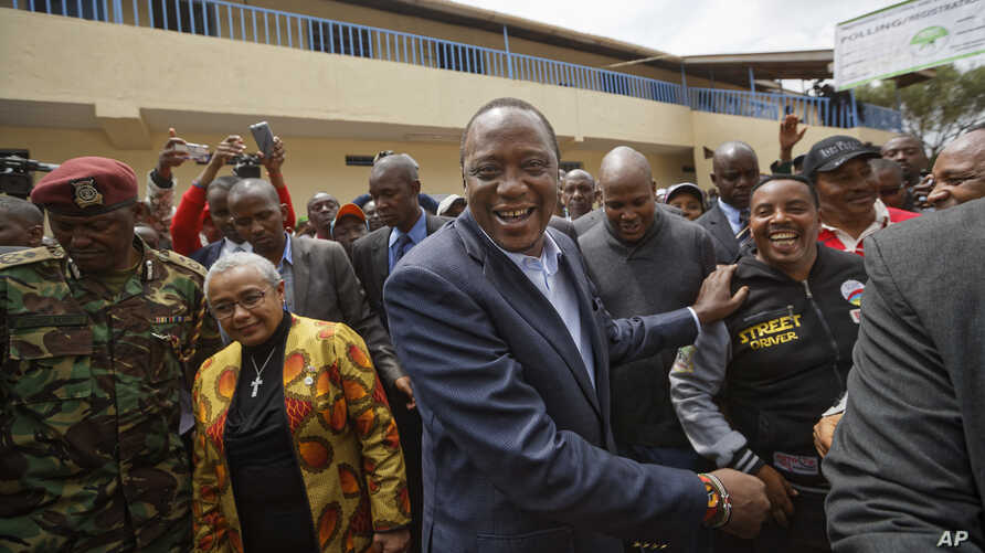 Kenya's President Uhuru Kenyatta shakes hands with supporters, accompanied by his wife, Margaret, center-left, after casting his vote in Gatundu, north of Nairobi, Aug. 8, 2017.