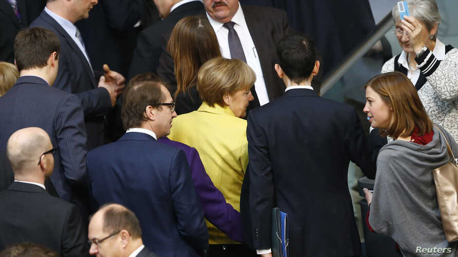 German Chancellor Angela Merkel (C) and fellow deputies leave after casting their vote on the approval to extend Greece's bailout, during a session of the Bundestag in Berlin, Feb. 27, 2015.