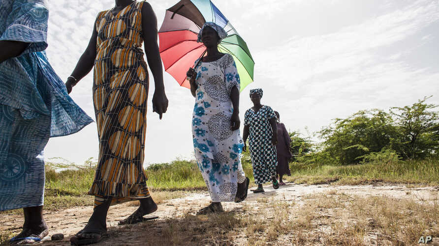 In this photo taken Monday, Oct. 19, 2015, women walk on farmlands that was destroyed by high salt content due to rising sea levels in Saloum Delta, Diamniadio Island in Senegal. Thousands of people on these tiny islands and villages in this part of