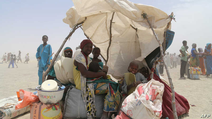 FILE - A handout photo released by the World Food Programme shows women and children evacuated from the islands of Lake Chad sitting under a makeshift tent in N'Guigmi, Niger, May 5, 2015.