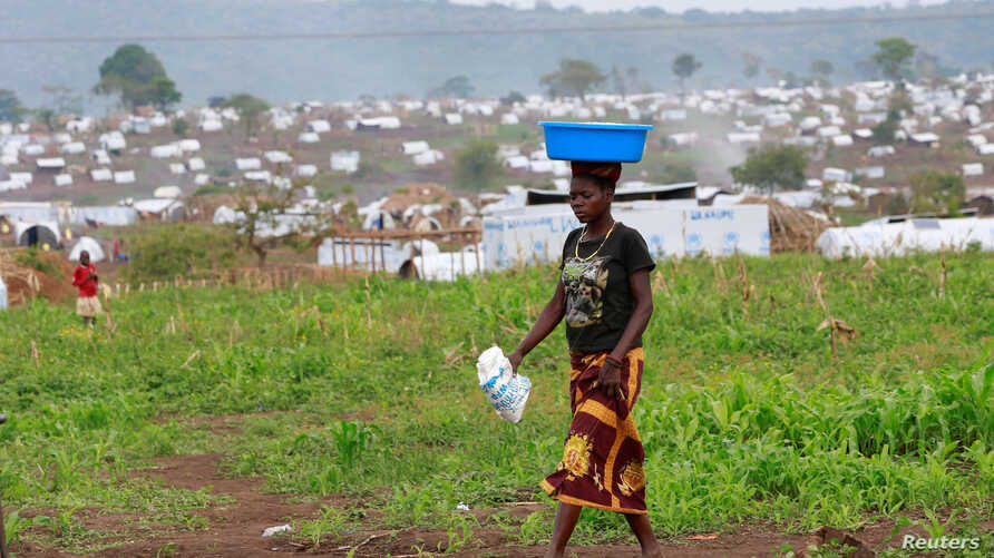 FILE - A Congolese woman, who fled ethnic fighting in the Democratic Republic of Congo on a fishing boat, across Lake Albert, carries belongings on her head at a UNHCR settlement camp in Kyangwali, Uganda, March 20, 2018.