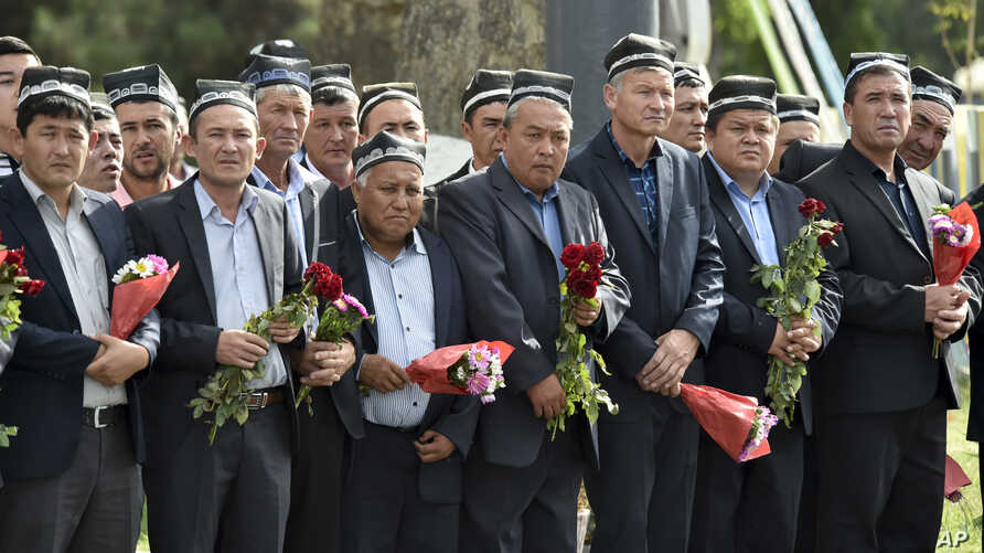 People hold flowers as they gather along the road to watch the funeral procession of President Islam Karimov in Samarkand, Uzbekistan, Saturday, Sept. 3, 2016.