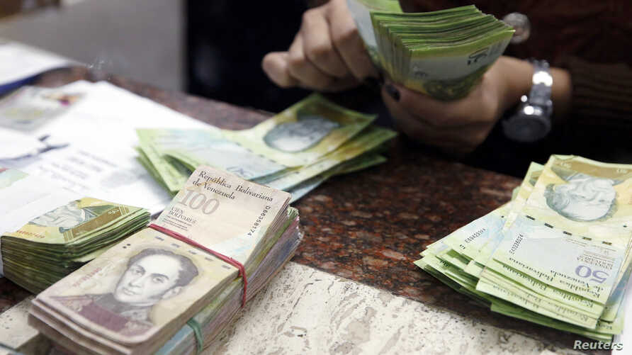 A cashier counts bolivars at a money exchange in Caracas, Venezuela, Feb. 24, 2015.