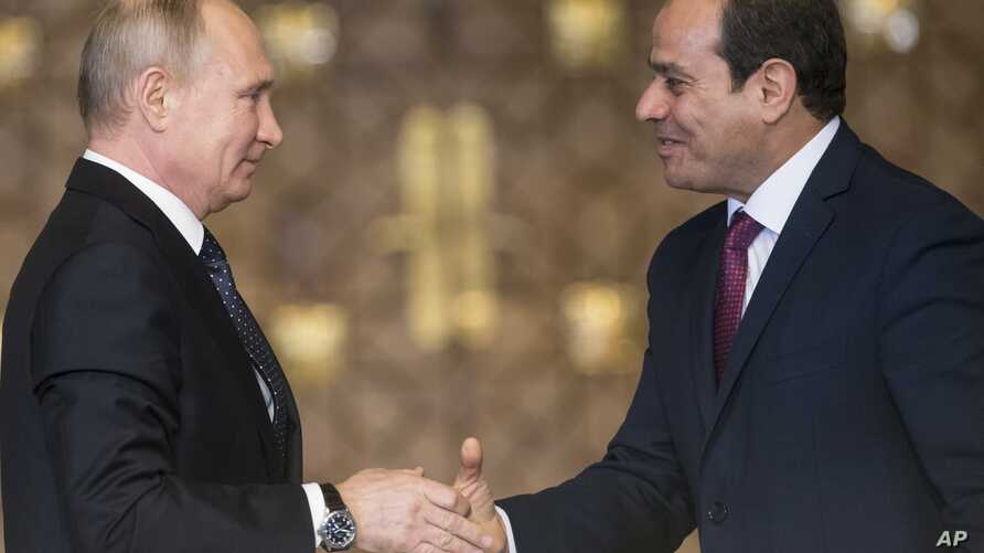 Russian President Vladimir Putin, left, Egyptian President Abdel-Fattah El-Sissi, shake hands after a news conference following their talks in Cairo, Egypt, Dec. 11, 2017.