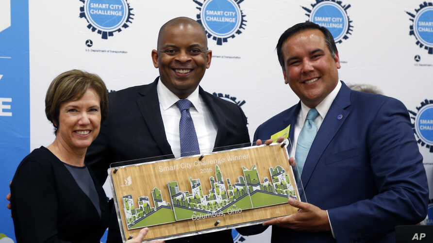 FILE - Barb Bennett, left, president/COO of Vulcan Inc, and U.S. Transportation Secretary Anthony Foxx, center, present the Smart City Challenge award to Columbus, Ohio, Mayor Andrew Ginther in Columbus, Ohio, June 23, 2016.