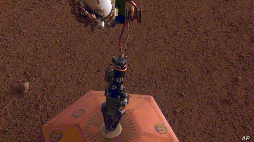 FILE - This photo provided by NASA Jet Propulsion Laboratory, shows the new Mars lander placing a quake monitor on the planet's dusty red surface. The unprecedented milestone occurred less than a month after Mars InSight's touchdown. InSight's roboti